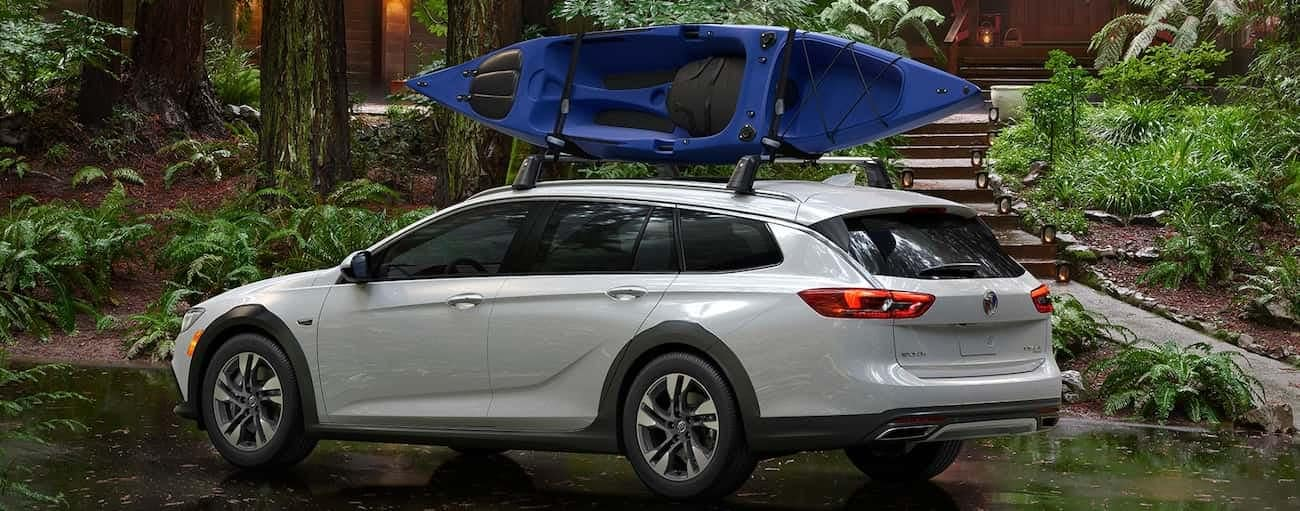 A white 2019 Buick Regal with a blue kayak on the roof outside a small cabin