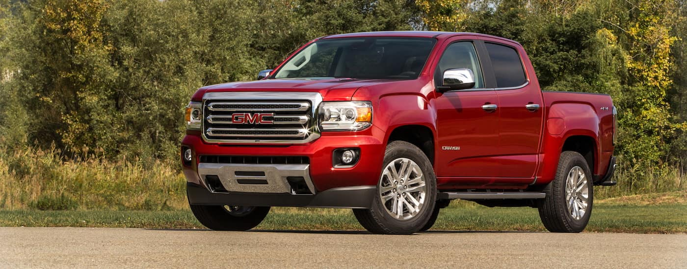 A red 2019 GMC Canyon with trees in the back