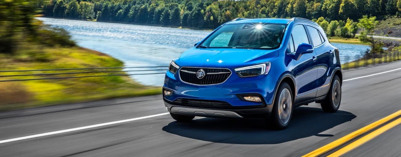 A blue 2019 Buick Encore is driving in front of a pond and greenery.