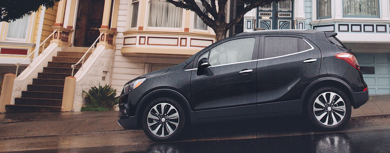 A black 2019 Buick Encore is parked on a steep street with colorful houses behind it.