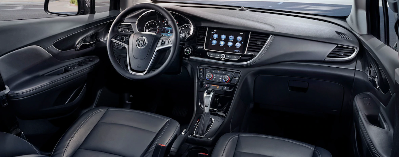 The black interior of a 2019 Buick Encore is shown. The entertainment features of the Encore are better when comparing the 2019 Buick Encore vs 2019 Chevy Trax.