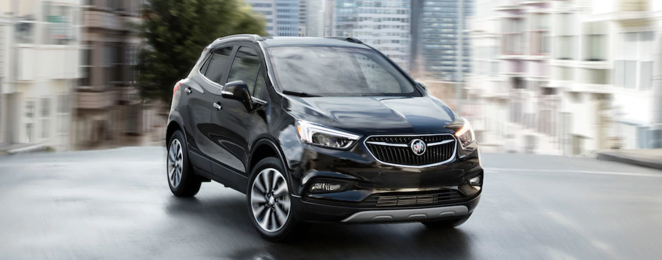 A black 2019 Buick Encore is taking a corner on a city street.