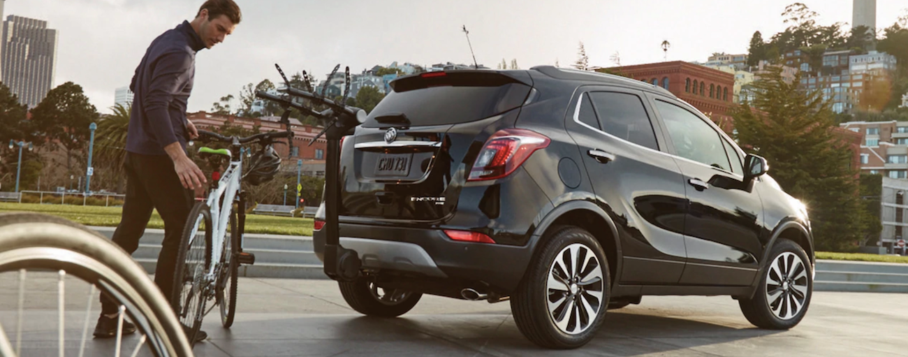 A man is putting his bike on the back of a black 2019 Buick Encore. Check out safety ratings when comparing the 2019 Buick Encore vs 2019 Ford EcoSport.