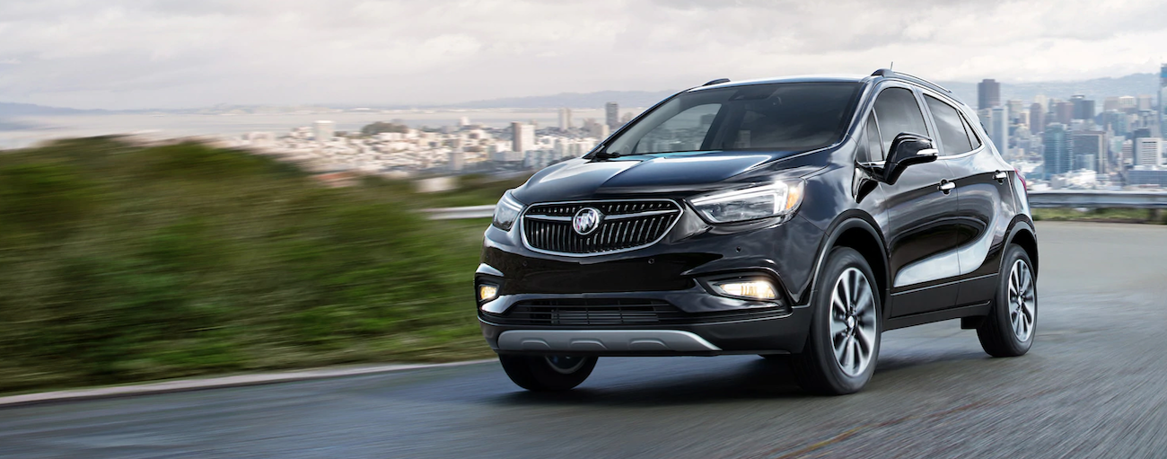 A black 2019 Buick Encore is driving away from a city blurred out in the background.