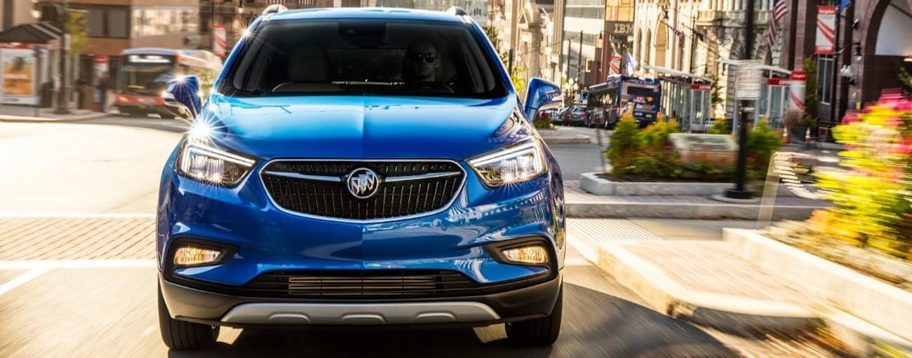 A blue 2019 Buick Encore on a busy city street