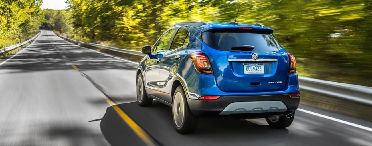 The rear view of a blue 2019 Buick Encore on a tree line road is displayed.