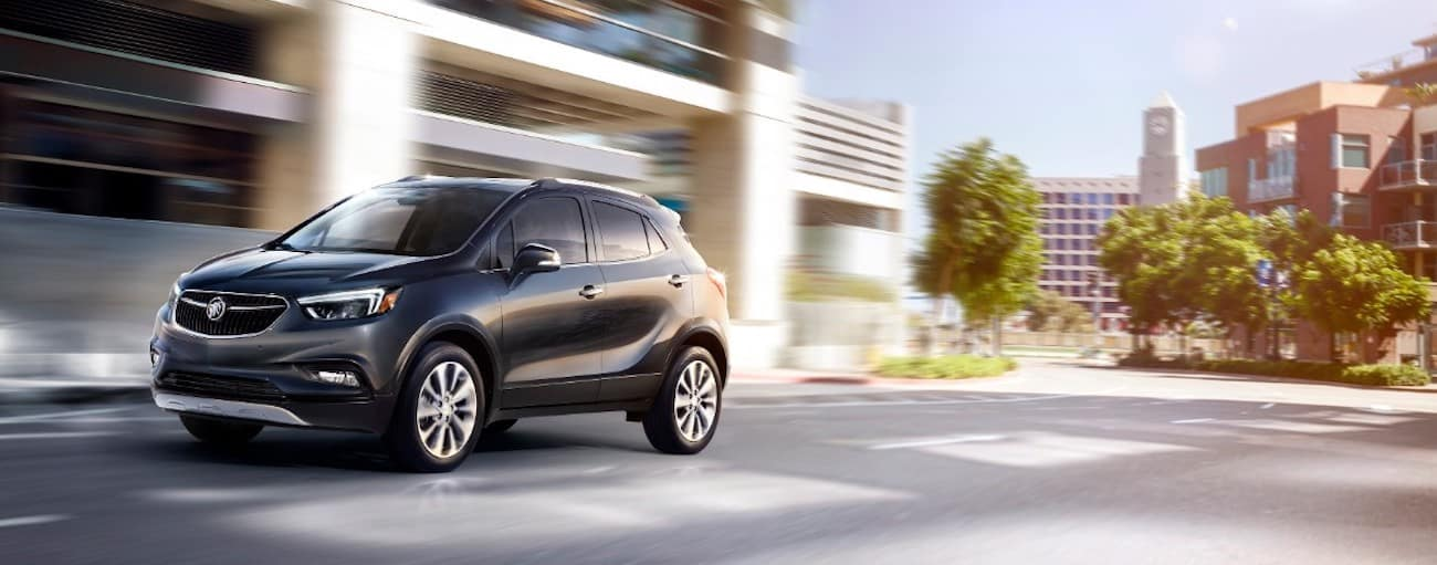 A black 2019 Buick Encore is driving down a sunny town street.