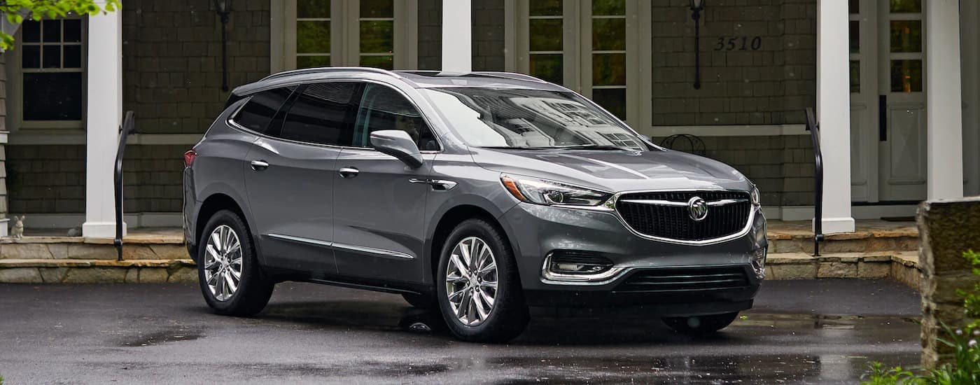 A grey 2019 Buick Enclave is parked outside a house