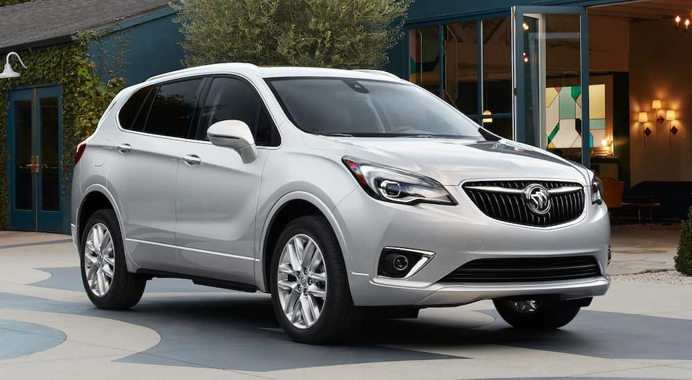 """A silver 2019 Buick Envision is parked on patterned concrete. Find one at Rick Hendrick or by searching """"Buick dealership near me in Atlanta, GA""""."""
