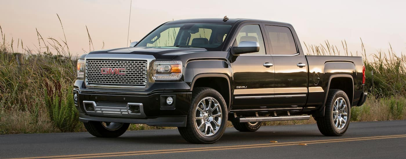 A black 2014 GMC Sierra 1500 is parked next to a grassy field at dusk.