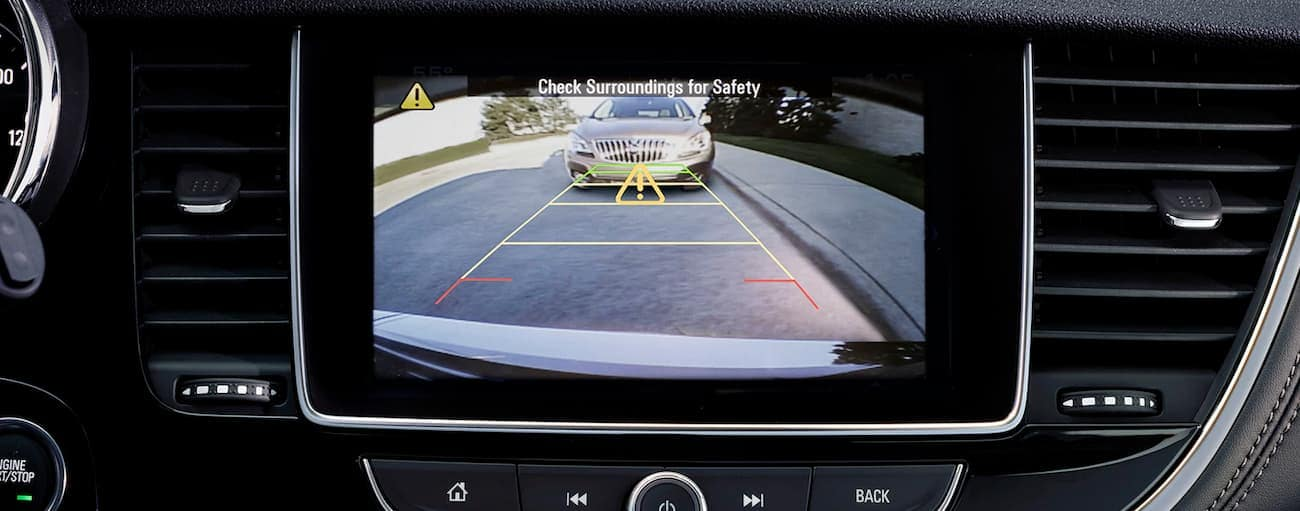 The screen of a Buick Encore shows the back up camera as it is reversing into a parking spot in Atlanta, GA.