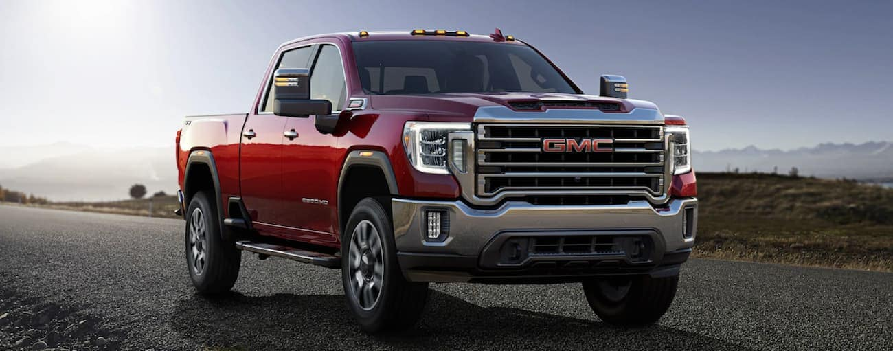 A red 2020 GMC Sierra 2500HD is driving on a highway outside of Atlanta, GA, with mountains in the distance.