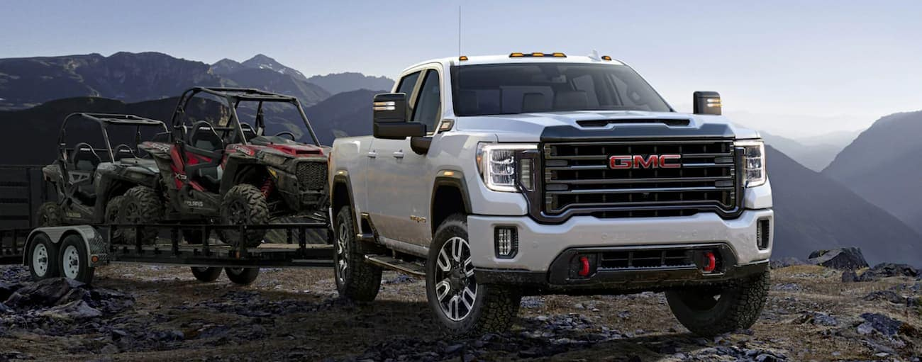A white 2020 GMC Sierra 2500HD is towing a trailer with side-by-sides on it.