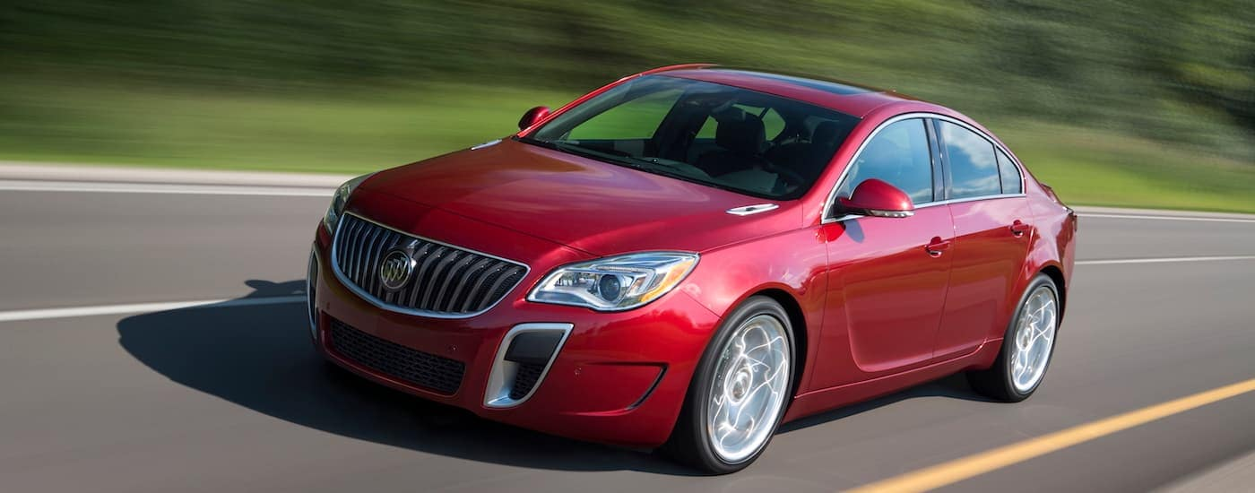 A red 2017 Buick Regal GS is diving in front of greenery near Atlanta, GA.