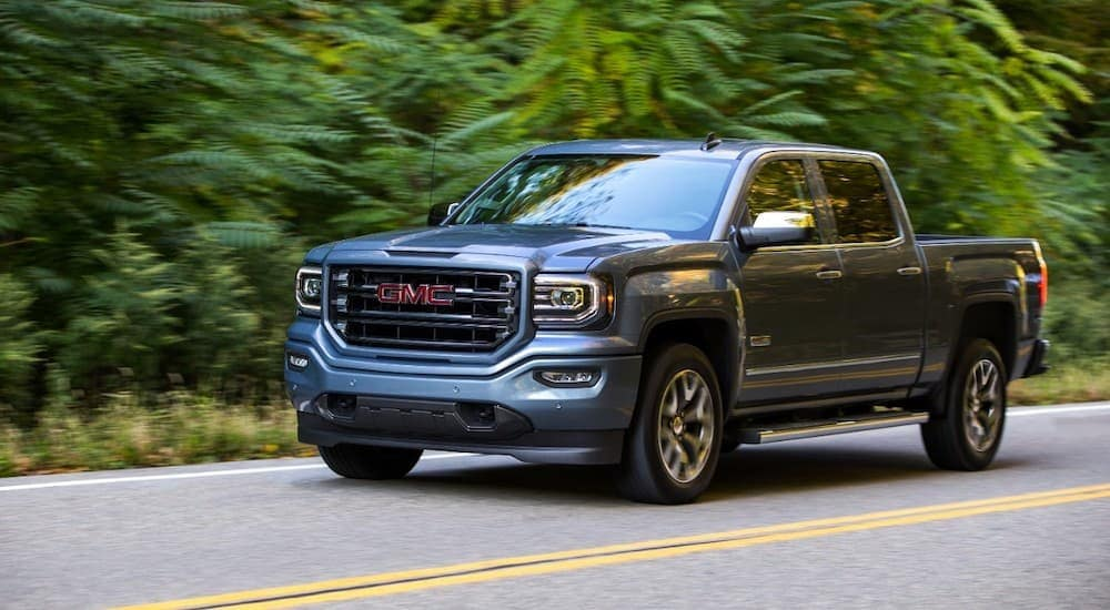 A grey 2017 GMC Sierra 1500, a popular choice for used trucks, is driving in front of trees outside Atlanta, GA.