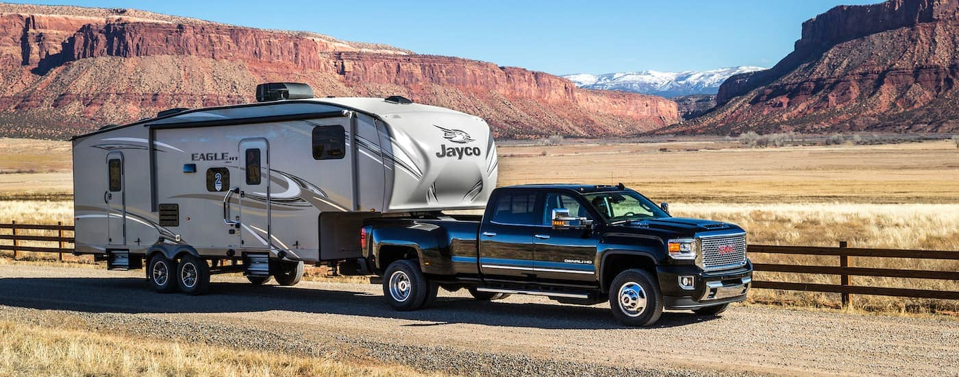 A black 2017 GMC Sierra Denali 3500HD is towing a camper through farm land with desert and mountains in the distance.