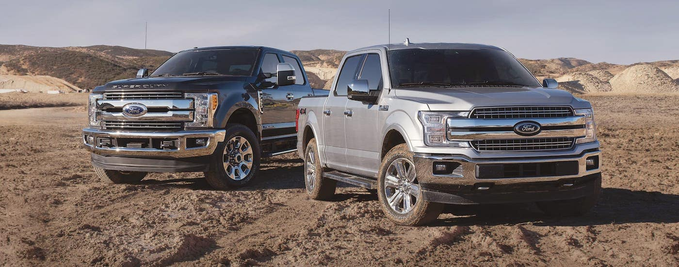A silver 2018 Ford F-150 and a black Ford Super Duty are parked in a desert.