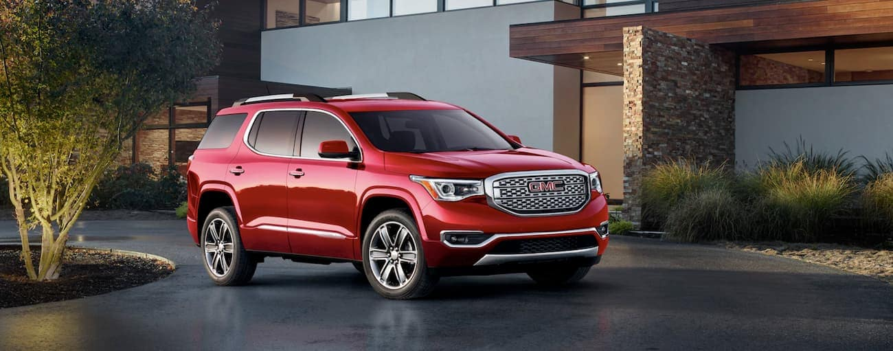 A red 2019 GMC Acadia is parked in the driveway of a modern house near Atlanta, GA.