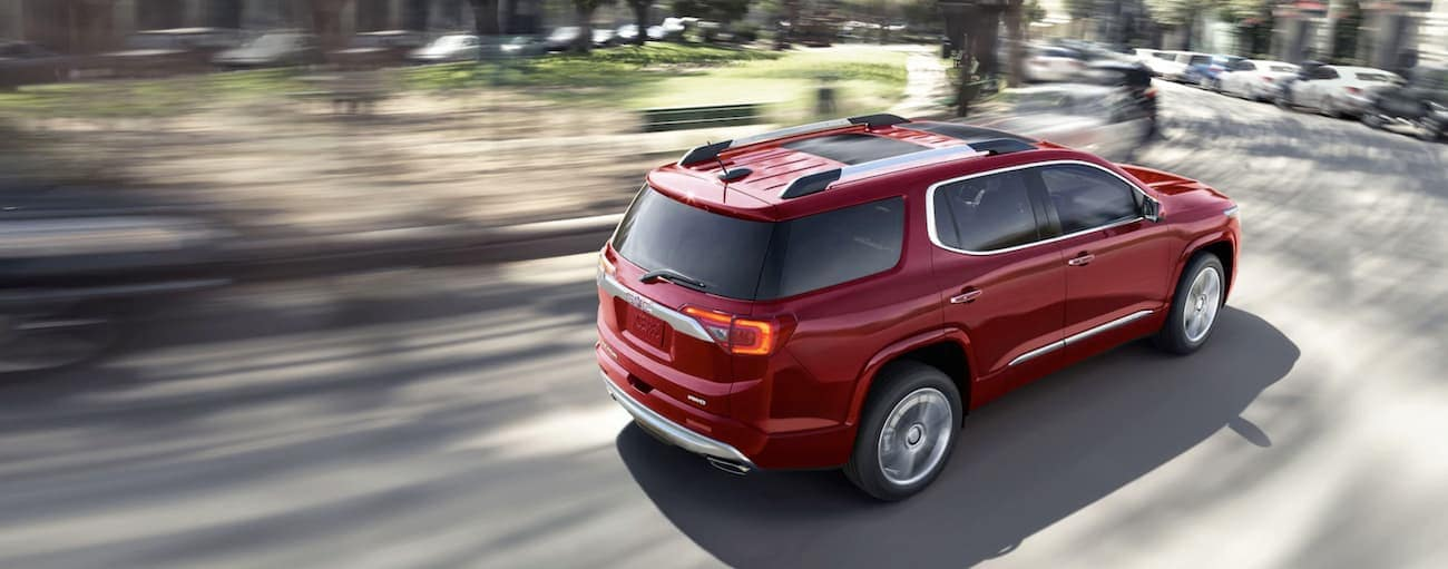 A red 2019 GMC Acadia is is driving downtown with a blurred background near Atlanta, GA.