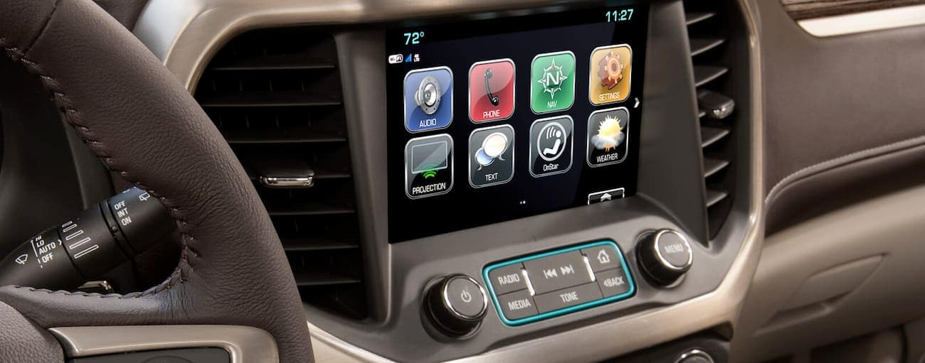 The touch screen in the brown interior of the 2019 GMC Acadia is shown. Check out entertainment when comparing the 2019 GMC Acadia vs 2019 Honda Pilot in Atlanta, GA.