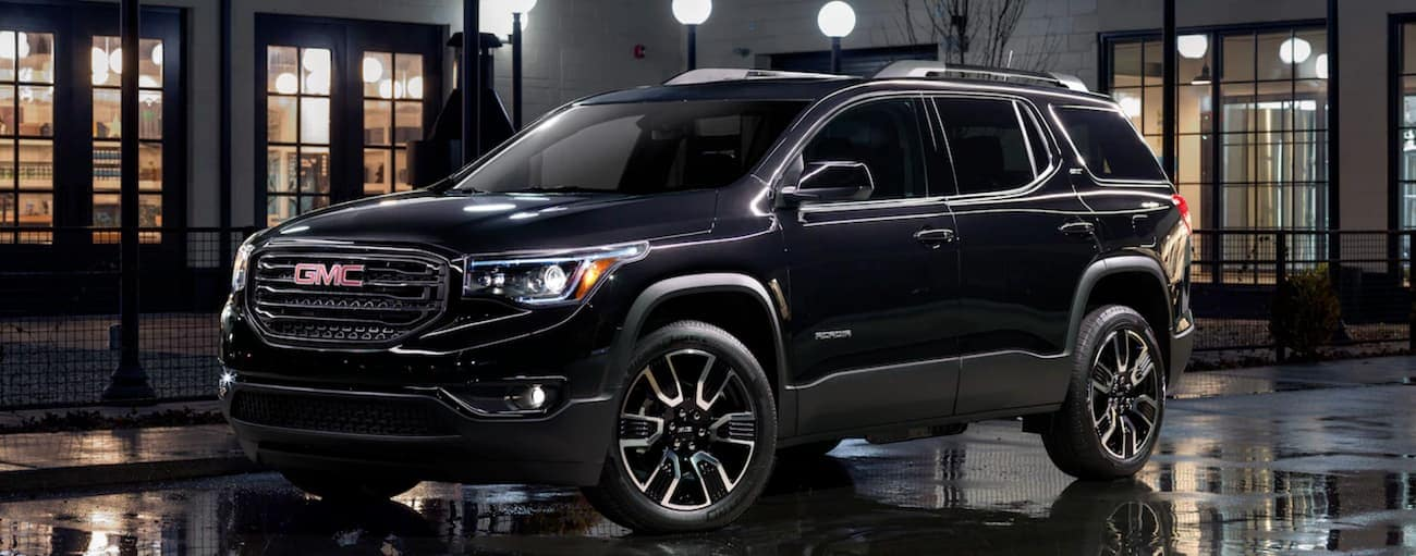 A 2019 GMC Acadia Black Edition is parked on a wet road at night in Atlanta, GA.
