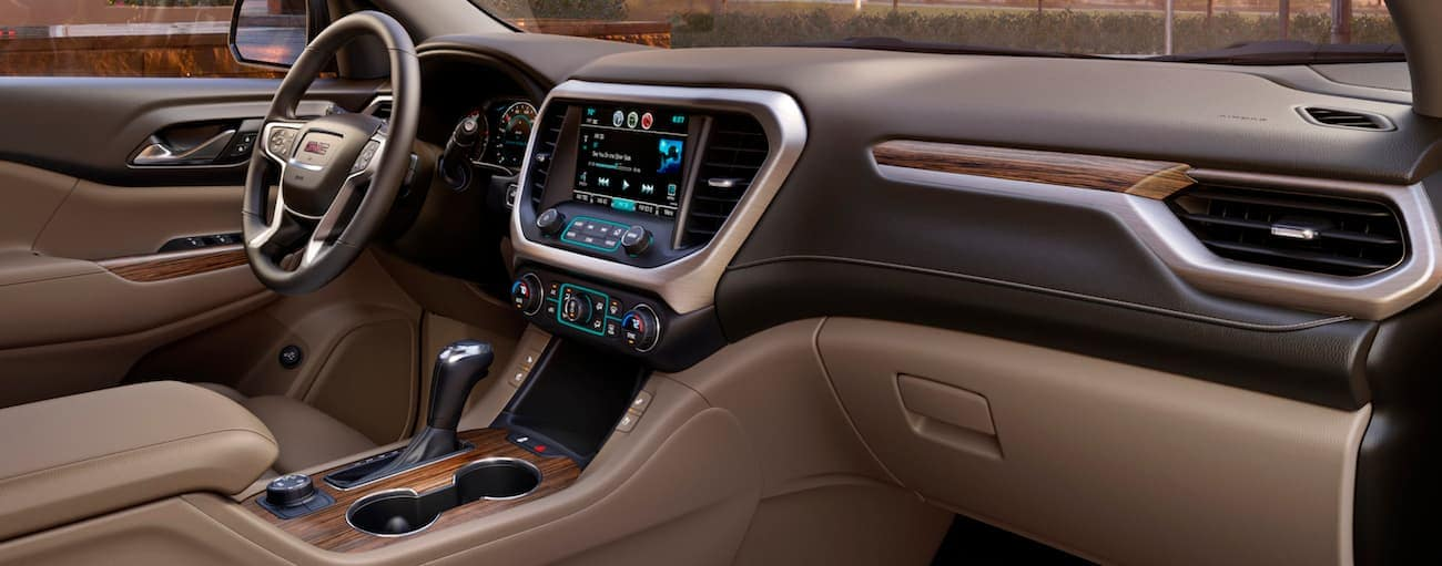 The brown and tan interior of a 2019 GMC Acadia is shown, which wins when comparing the 2019 GMC Acadia vs 2019 Toyota Highlander.
