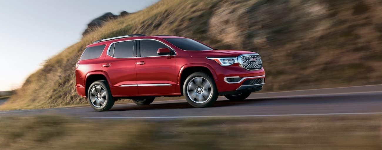 A red 2019 GMC Acadia Denali is driving fast past a hill.