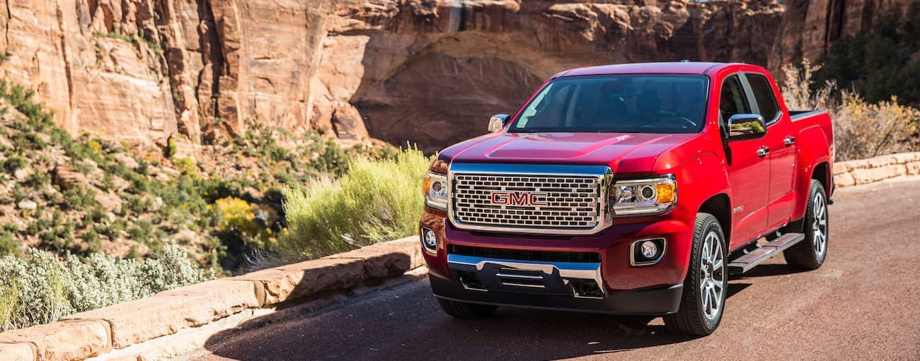 A red 2019 GMC Canyon, which wind=s when comparing the 2019 GMC Canyon vs 2019 Ford Ranger is driving past red desert rocks.