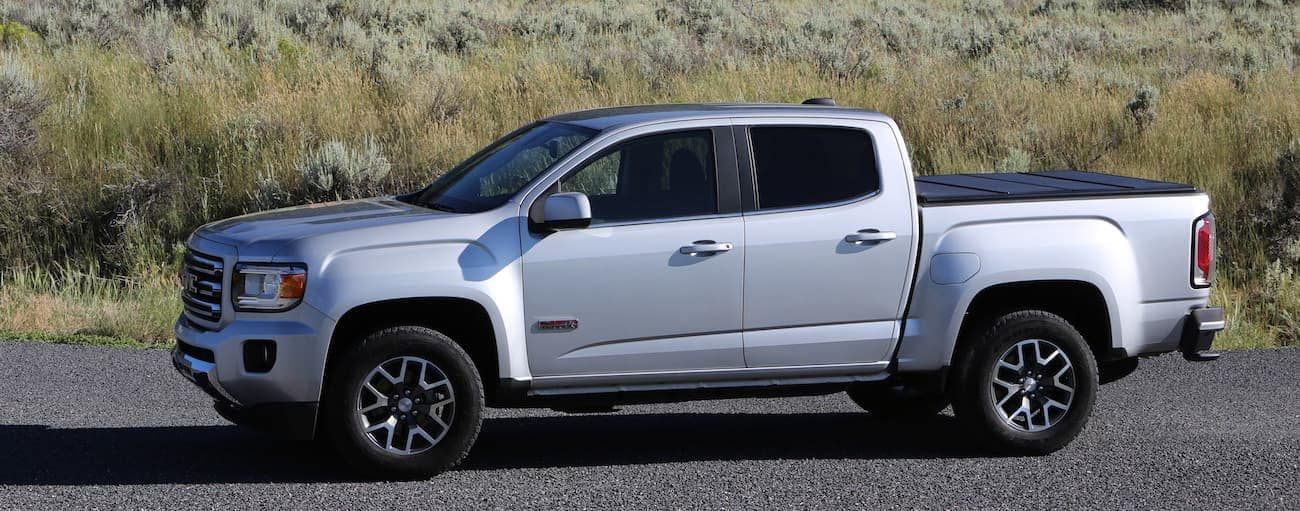 A silver 2019 GMC Canyon is parked in front of tall grass outside Atlanta, GA.