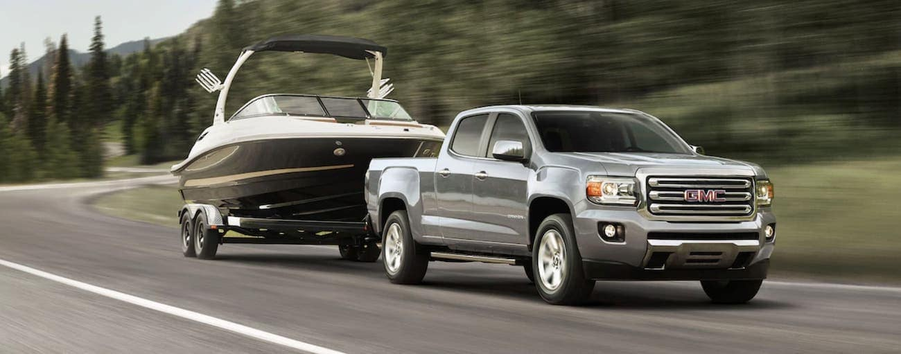 A grey 2019 GMC Canyon, which wins when comparing the performance for the 2019 GMC Canyon vs 2019 Toyota Tacoma, is towing a boat.