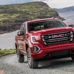 After leaving an Atlanta GMC dealer, a 2019 GMC Sierra 1500 AT4 is shown driving on a dirt road hill with a lake and mountains in the background.