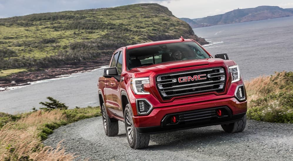 After leaving an Atlanta GMC dealer, a 2019 GMC Sierra 1500 AT4 is shown driving on a dirt road with a lake and mountains in the background.