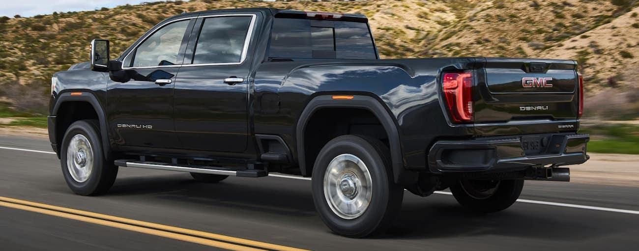 A black 2020 GMC Sierra 2500HD is driving on a road next to large dirt hills near Atlanta, GA.