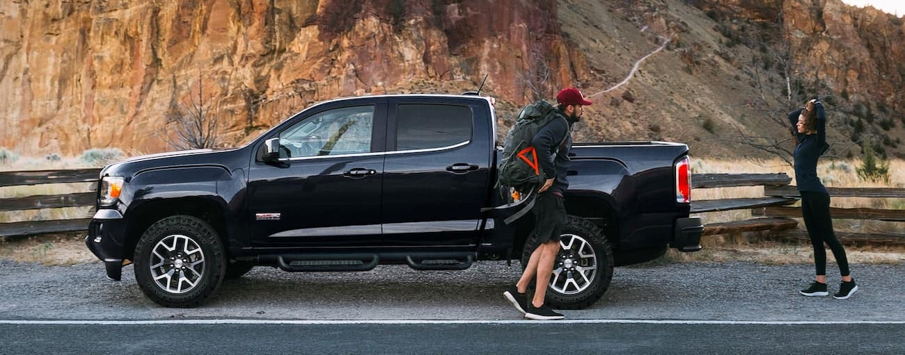 Two hikers are walking away from a black 2019 GMC Canyon outside Atlanta, GA.