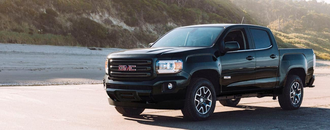 A black 2019 GMC Canyon is on a beach with a hill behind it.