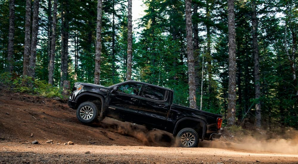 A 2019 GMC Sierra AT4 is shown driving in the woods climbing a hill after leaving an Atlanta GMC dealer.