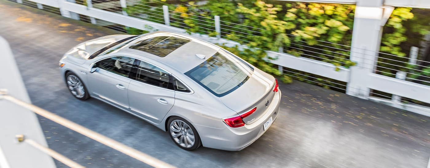 A silver 2017 Buick LaCrosse, which you can find models by searching 'used car dealership near me', is shown from above on a bridge.