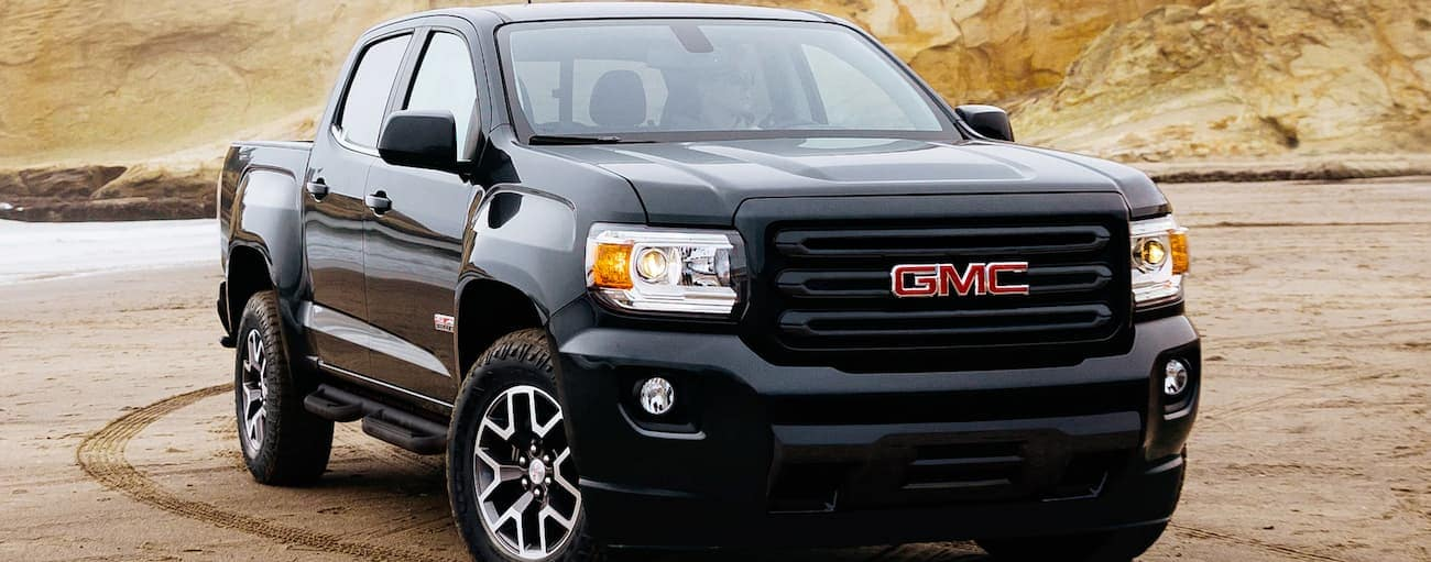 A black 2019 GMC Canyon, which wins when comparing the 2019 GMC Canyon vs 2019 Nissan Frontier, is on a beach.