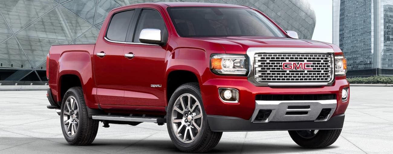 A red 2019 GMC Canyon Denali is parked in front of glass buildings near Atlanta, GA.