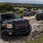Three black 2017 GMC Sierra 2500HDs are on a rocky road.