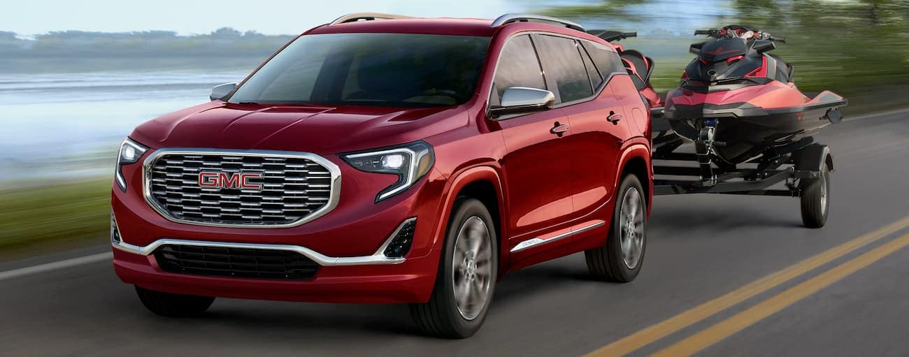 A red 2019 GMC Terrain is towing red jet skis.
