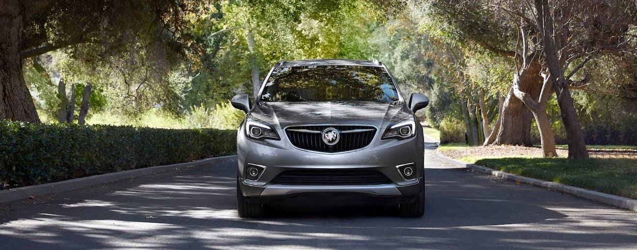 A grey 2020 Buick Envision is on a tree-line street near Atlanta, GA.