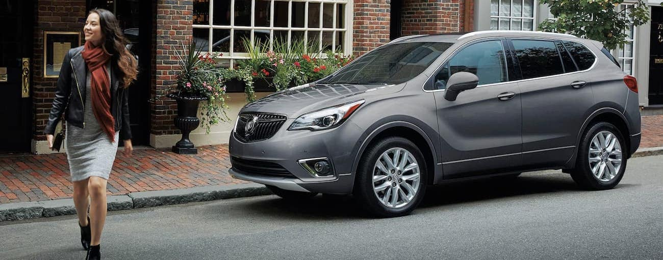 A woman is walking away from her 2020 Buick Envision in front of a brick building.