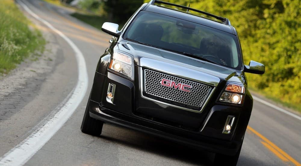 A black 2015 GMC Terrain Denali, popular among used SUVs for Sale in Atlanta, GA, is driving on a tree-lined road.