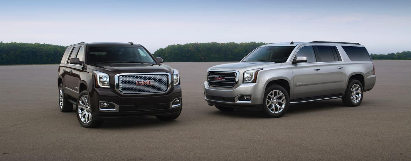 A black 2015 GMC Yukon and a silver XL are parked in an open parking lot.