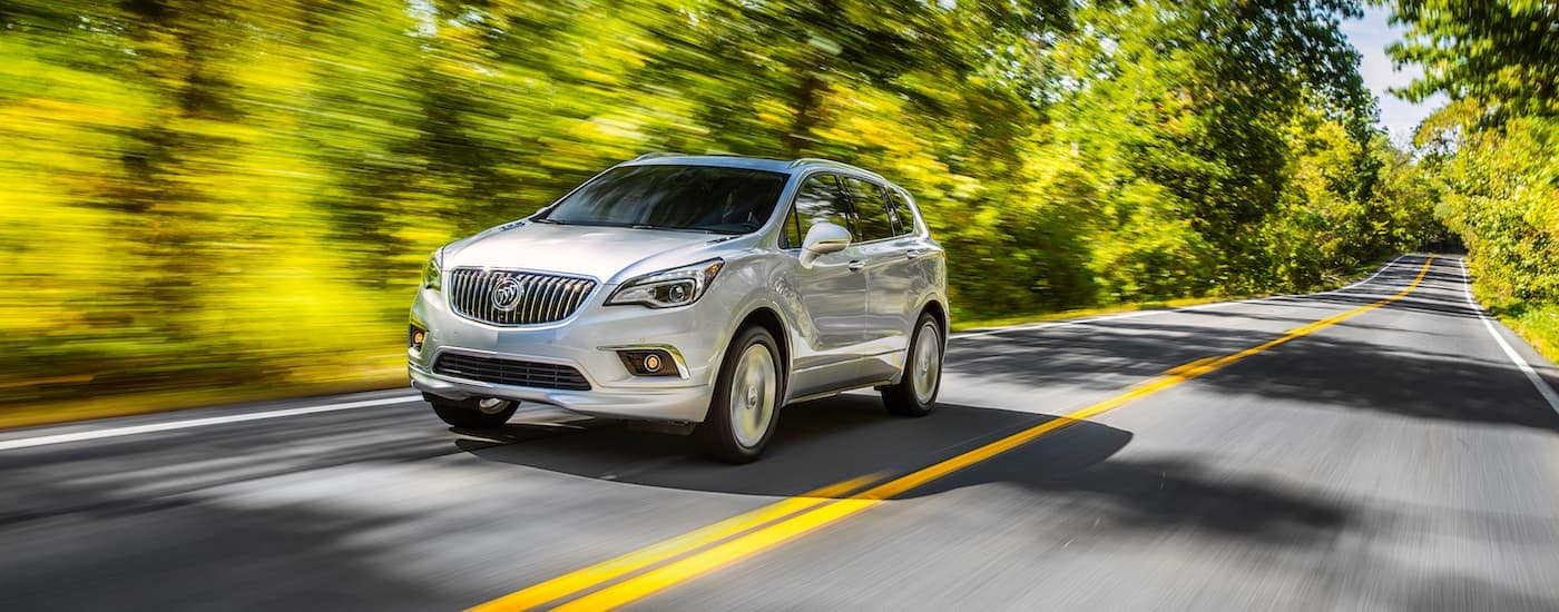 A white 2017 Buick Envision is driving on a sunny, tree-lined road.