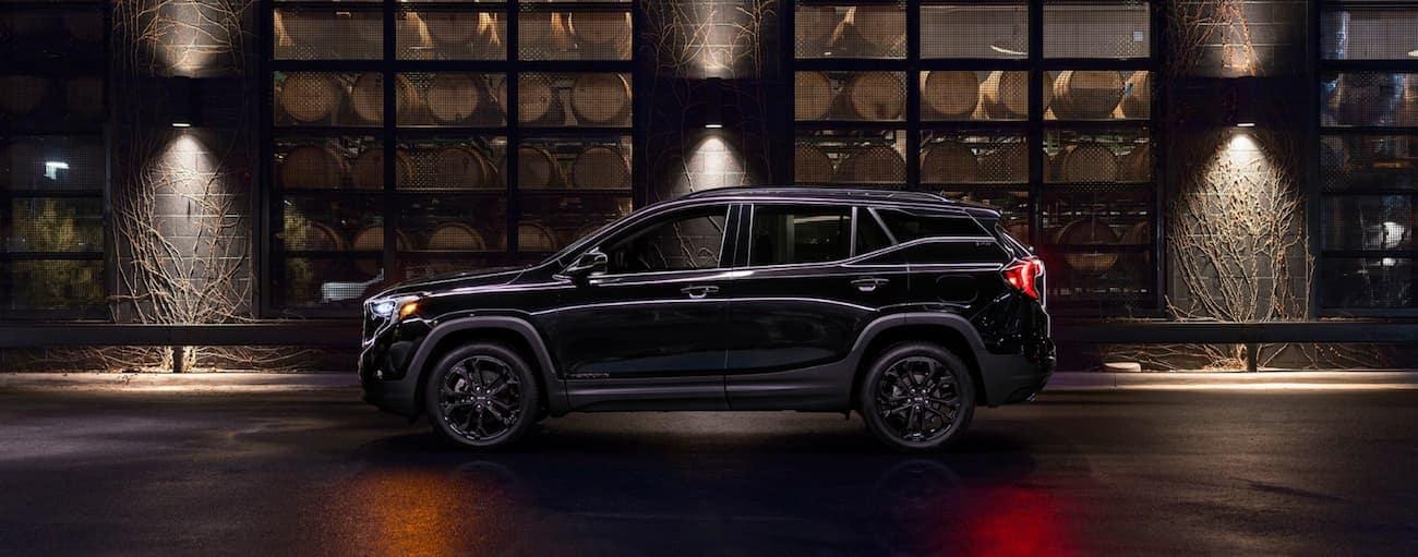 A black 2019 GMC Terrain is parked on a dark lit street.