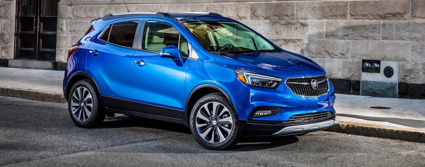 A blue 2019 Buick Encore is parked in front of a gray stone building.