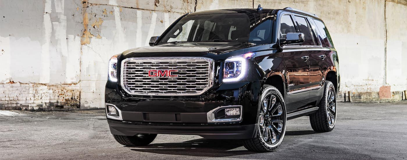 A luxurious used SUV for sale, a black 2019 GMC Yukon Denali, is parked in front of a concrete wall.