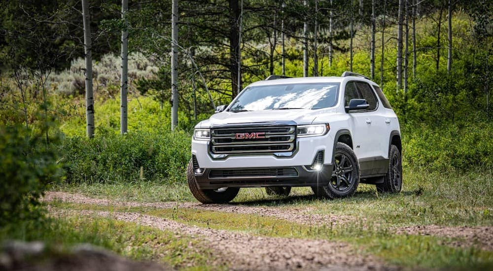 A white 2020 GMC Acadia AT4 is parked on a dirt trail.